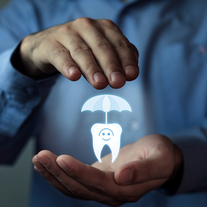 Hand holding animted tooth under umbrella representing dental insurance protection