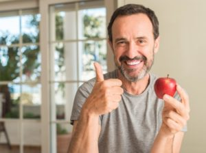 Man in grey shirt smiling eating apple